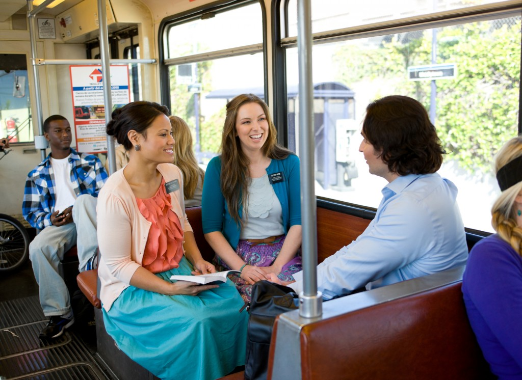 Sister Missionaries talking to a man on a train
